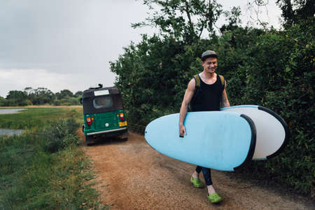 a man happily carries two surfboards from a taxi on the way Stock Photo