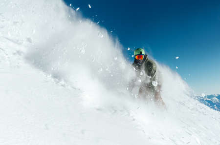 man snowboarder is going very fast freeride in the stream of snow avalanche 写真素材