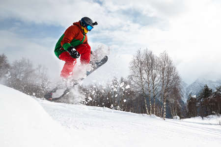 guy snowboarder takes grab jumping from a springboard in the forest