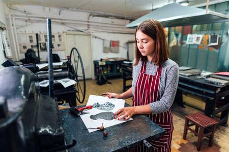 girl prints linocut on the machine Stock Photo