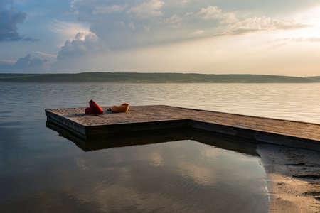 pier with beanbag at the calm lake at sunset 版權商用圖片