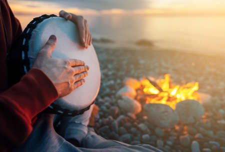 percussionist plays djembe on the seashore near the fire, hands close up
