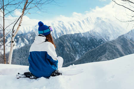 Girl with ski mask in blue suit sits on snowboard in snow looking at mountains.