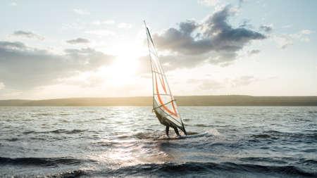Morning windsurfing on a lake with little fog sunrise