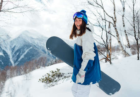 laughing happy girl with snowboard and ski mask on background of mountains and snowy trees. 版權商用圖片