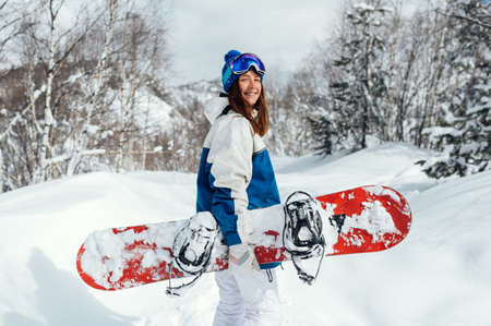smiling happy girl with snowboard and ski mask on background of mountains and snowy trees.