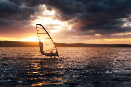 Windsurfing on a lake at sunset, contrast scene.