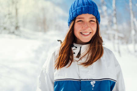 portrait of teenage girl in blue winter sports suit on background of snowy trees.