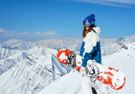 cheerful girl snowboarder on the background of peaks of snowy mountains 版權商用圖片
