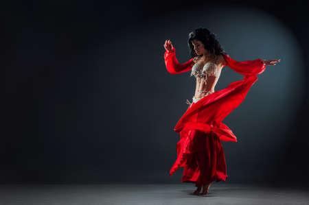 Hermosa chica de pelo negro con un vestido rojo étnico en el escenario bailando danza oriental agitando su falda