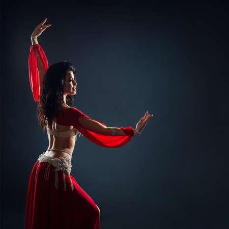 Hermosa chica de pelo negro con un vestido étnico rojo bailando bailes orientales en la oscuridad