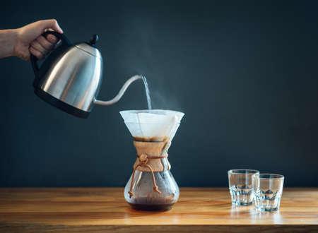 Kaffee mit einer alternativen Methode zubereiten, heißes Wasser aus dem Wasserkocher in eine Glaskaraffe auf einem Holztisch und grauem Hintergrund gießen, minimalistische Seitenansicht side
