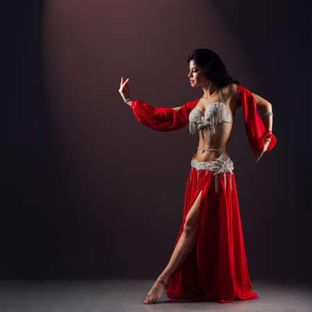 beautiful girl in red ethnic dress dancing oriental belly dance on stage