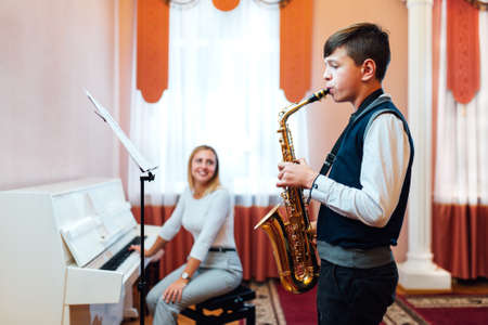 A student boy in a saxophone lesson learns to play the accompaniment of a cheerful teacher on the piano