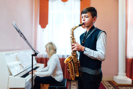 A teenage boy learns to play the saxophone in a music lesson to accompaniment of a female teacher on the piano.