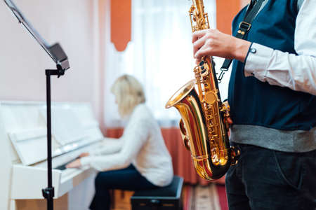Student saxophone at a lesson in a music school close-up on the background of a teacher at the piano Banque d'images