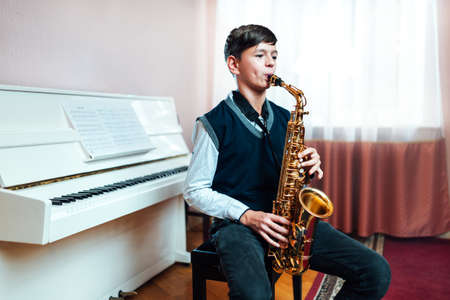 boy student plays the saxophone while sitting at a music lesson in class on the background of the piano