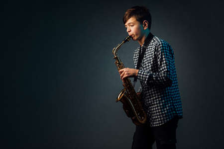 A boy on a dark background with a searchlight plays the saxophone