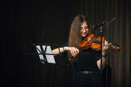 Classical female musician playing the violin on stage during a recital or live performance