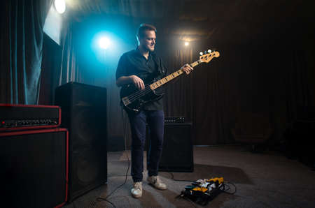 Musician playing an electric bass guitar on stage Stock Photo