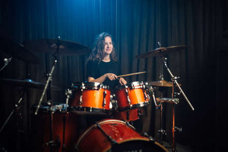 Woman playing drums during a live performance