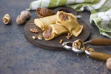 condensed: Pancakes with condensed milk boiled. Walnut  Stock Photo