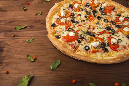 bakery products: Pizza ham with cheese, tomatoes and pepper. Close-up on a wooden background