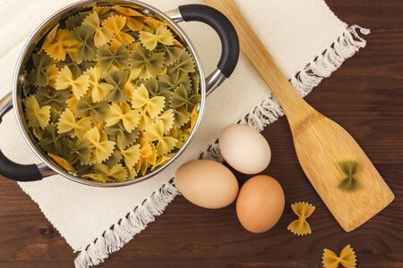 Macaroni farfalle colored in a saucepan. Three colors. On a napkin and a wooden background