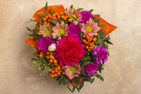 A beautiful bouquet of flowers with a rowanberry. View from above. On a textured, light background Stock Photo