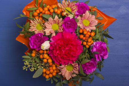 Een mooi boeket bloemen met een lijsterbes. Bekijk van bovenaf. Op een blauwe achtergrond