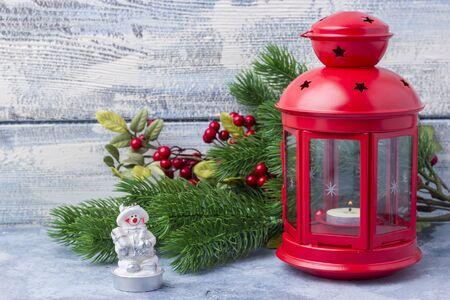 Candelabro rojo con una vela adentro y una rama de un árbol de Navidad. Tema del Año Nuevo y la Navidad Foto de archivo