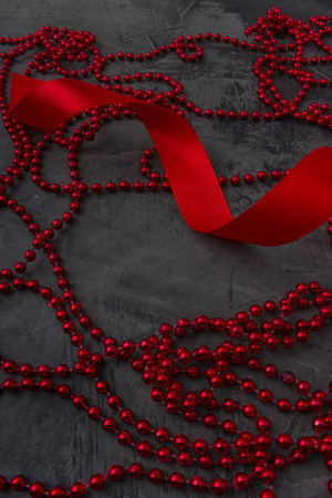 Decoration and red ribbon on a dark background. Space for text