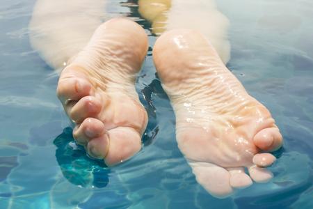 Beautiful female legs relax in clear water. Foot sole after peeling