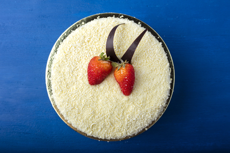 Cake with white chocolate and fresh strawberries. Delicious dessert on a blue background. View from above  Stock Photo