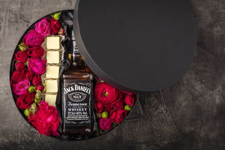 NOVOSIBIRSK, RUSSIA - FEBRUARY 23, 2018 - gift wrapping of JackDaniels whiskey. Cubes from Belgian white chocolate. Flowers and alcohol Editorial