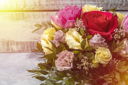 A beautiful bouquet of roses and other flowers on a light background