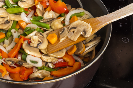 Stirring vegetables with mushrooms in a frying pan on a dark background. Cooking food Reklamní fotografie