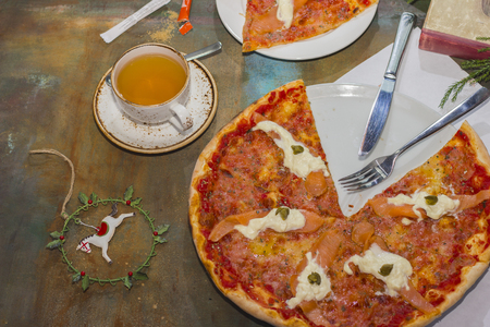 Pizza with red fish and cheese. Seafood. A cup of tea
