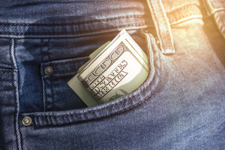 Banknotes of hundreds of US dollars are twisted into a tube, sticking out of a pocket of jeans. American currency. Copy space Imagens
