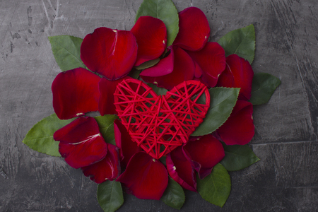Red heart in the leaves of a rose on a dark background. Space for text