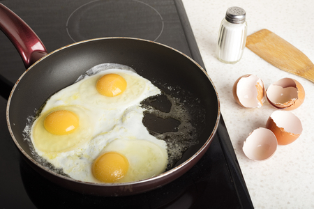 Fried 3 eggs fried in a frying pan. Hot appetizing dish. Food bachelor 1