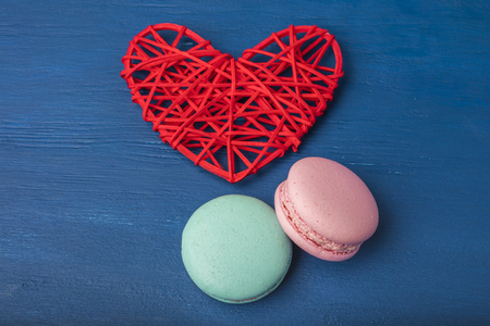 Pink and turquoise cookies, macaroni and red heart on a blue background. Close-up. Copy space 免版税图像