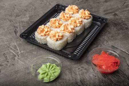 Japanese rolls lie on a black plate. Traditional food in Japan