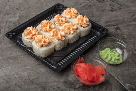 Japanese rolls lie on a black plate. Traditional food in Japan Stock Photo - 124399593
