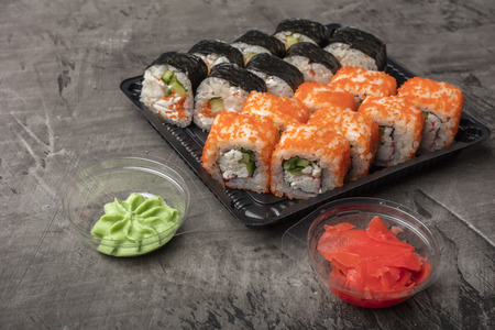 Japanese rolls lie on a black plate. Traditional food in Japan Stock Photo - 124399614