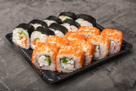 Japanese rolls lie on a black plate. Traditional food in Japan Stock Photo - 124399651