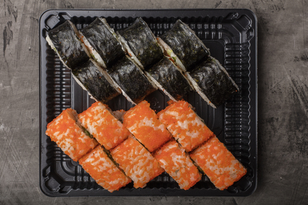 Japanese rolls lie on a black plate. Traditional food in Japan. View from above Stock Photo