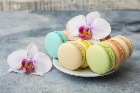 Colorful macarons in a plate on blue background. Macaron or Macaroon is sweet meringue-based confection. Decorated with orchid flowers Standard-Bild - 124399897