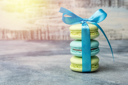 Delicious sweet colorful cookies macaron, macaroon with blue bow on a light background Standard-Bild - 124400082