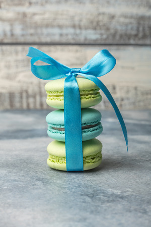 Delicious sweet colorful cookies macaron, macaroon with blue bow on a light background Standard-Bild - 124400288